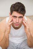 Close up of man suffering from headache in bed Royalty Free Stock Photos