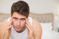 Close up of man suffering from headache in bed Royalty Free Stock Photo