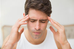 Close up of man suffering from headache in bed Stock Images