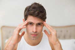 Close up of man suffering from headache in bed Royalty Free Stock Image