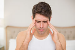 Close up of man suffering from headache in bed Stock Image
