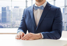 Close up of man in suit and bow-tie at table Stock Image