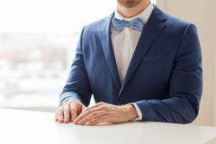 Close up of man in suit and bow-tie at table Stock Photography