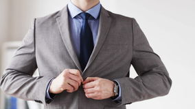 Close up of man in suit fastening button on jacket stock video footage