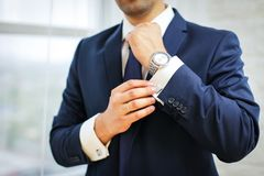 Close-up of man in suit with watch on his hand fixing his cufflink. groom bow tie cufflinks.  stock image