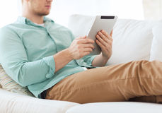 Close up of man with tablet pc computer at home. Technology, leisure, lifestyle and distance learning concept - close up of man working with tablet pc computer Royalty Free Stock Photo