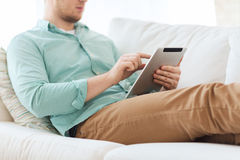 Close up of man with tablet pc computer at home. Technology, leisure, lifestyle and distance learning concept - close up of man working with tablet pc computer Stock Images