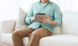 Close up of man with tablet pc computer at home. Technology, leisure, lifestyle and distance learning concept - close up of man working with tablet pc computer Royalty Free Stock Image