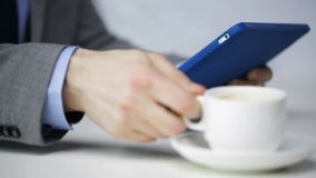 Close up of man with tablet pc drinking coffee stock footage
