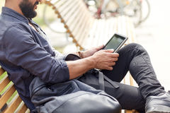 Close up of man with tablet pc sitting on bench Stock Photography