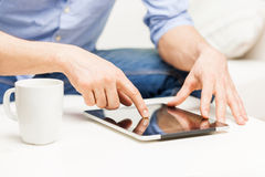 Close up of man with tablet pc and tea cup at home Royalty Free Stock Images