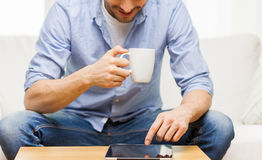 Close up of man with tablet pc and tea cup at home Royalty Free Stock Photography