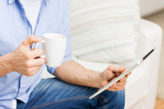 Close up of man with tablet pc and tea cup at home Royalty Free Stock Photo