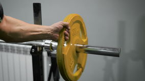Close-up of a man taking the metal weight plate. Close-up of a sportsman with muscular hand taking the metal weight plate away of barbell stock footage