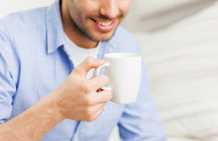 Close up of man with tea or coffee cup at home Royalty Free Stock Images