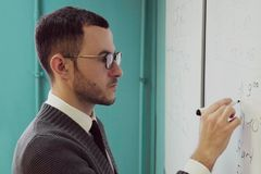 Man teacher in glasses writing on a whiteboard Royalty Free Stock Photography