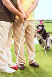 Close up of man teaching to play golf. Doing careful. Close up of old men teaching elder women to play golf on course Stock Photography