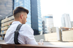 Close up of man texting on smartphone in city. Technology, communication and people concept - close up of man texting message on smartphone in city Royalty Free Stock Image