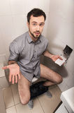 Close-up of man in toilet holding tissue. Royalty Free Stock Photography