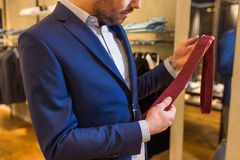 Close up of man trying tie on at clothing store Royalty Free Stock Photography