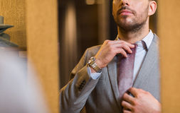 Close up of man trying tie on at mirror Stock Photography