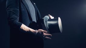 Close up of a man is twisting and turning his black top hat. 4K stock video footage