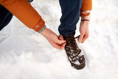 Close up of man tying boot shoelaces in winter. People, footwear and season concept - close up of man tying boot shoelaces outdoors in winter Royalty Free Stock Photos