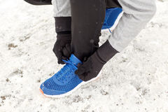 Close up of man tying shoe lace in winter outdoors Stock Photos