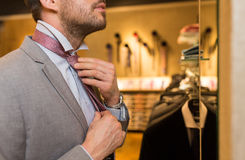 Close up of man tying tie at clothing store mirror Stock Photos