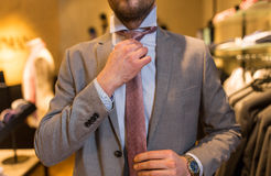 Close up of man tying tie at clothing store mirror Royalty Free Stock Photography