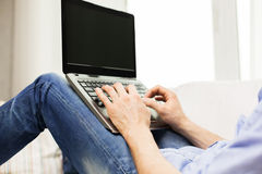 Close up of man typing on laptop computer at home Stock Image