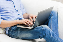 Close up of man typing on laptop computer at home Stock Photography