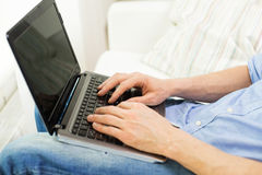 Close up of man typing on laptop computer at home Royalty Free Stock Photography