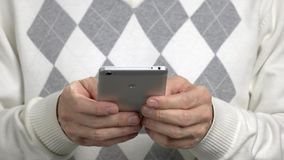 Close up man typing a message on smartphone. Man in sweater with rhombuses using his smartphone close up stock footage