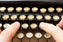 Close up of man typing with old typewriter Stock Image