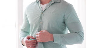 Close up of man unbuttoning his shirt at home Royalty Free Stock Photos