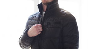 Close up of man unzipping his black jacket at home. Clothes, fashion and dressing concept - close up man unzipping his black jacket at home stock video footage
