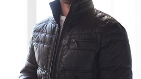 Close up of man unzipping his black jacket at home. Clothes, fashion and dressing concept - close up man unzipping his black jacket at home stock footage