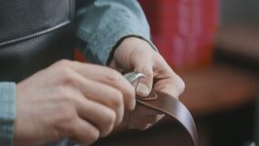 Close up of man uses a needle to crafts a brown leather belt in the leather workshop. Working process of the leather