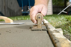 Close up of man finishing cement with edging tool royalty free stock photo