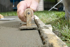 Close up of a man using edging tool on wet cement. A close up of a man using a concrete edging tool on wet cement slab with timber form work Stock Photography