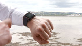 Close up of a man using his smart watch. At the beach stock video footage