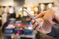 Close up of a man using mobile  phone in clothing store Stock Image