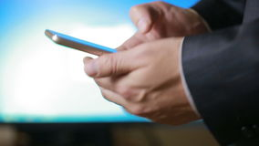 Close up of a man using mobile smart phone. the background monitor. Close up of a man using mobile smart phone stock video