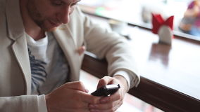 Close up of a man using mobile smart phone. In a cafe stock video
