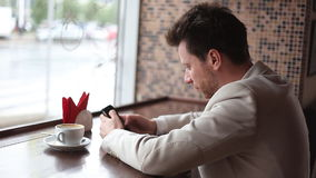 Close up of a man using mobile smart phone. In a cafe stock video footage