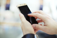 Close up of a man using mobile smart phone. In modern office Stock Photography