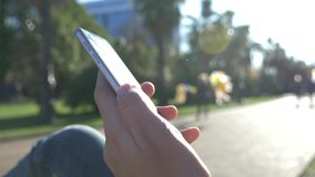 Close up of a man using a mobile smart phone, outdoor. Close up of a male hands texting on his smartphone in the city stock video footage