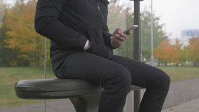Close-up of a man using smart phone at a bus stop. Close-up of a man sitting at a bus stop a gray and cloudy day using a smart phone stock footage