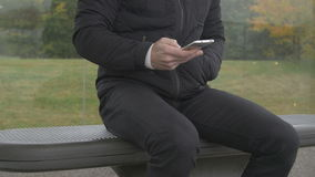 Close-up of a man using smart phone at a bus stop. Close-up of a man sitting at a bus stop a gray and cloudy day using a smart phone stock video